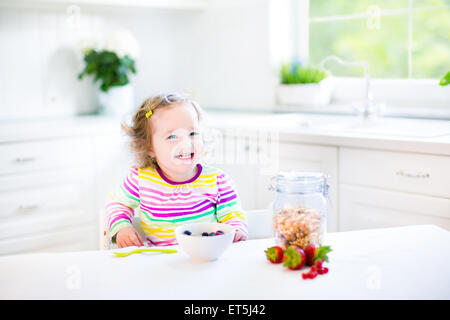 Beautiful toddler girl with curly hair wearing a colorful shirt having breakfast drinking juice in a white sunny - Stock Photo