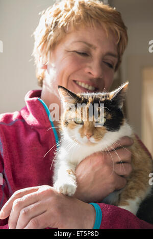 Close-up of mature woman with cat in her arms, Bavaria, Germany - Stock Photo