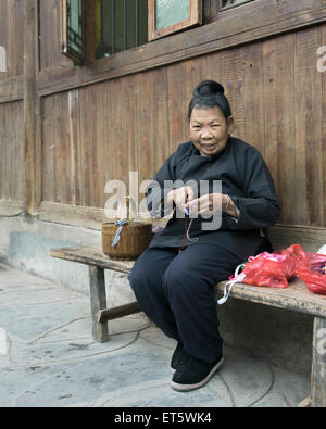 Dong woman at her handicrafts, Zhaoxing Dong Village, Guizhou Province, China - Stock Photo