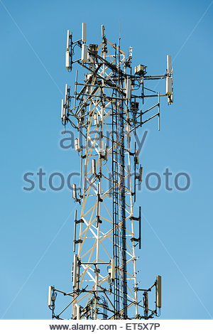 Cell phone communication tower with multiple antennas against a blue sky - Stock Photo