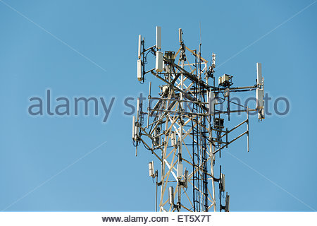 Top part of cell phone communication tower with multiple antennas against a blue sky - Stock Photo