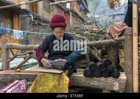 Fast hands_woman rolling indigo-dyed traditional cloth, Zhaoxing Dong Village, Guizhou Province, China - Stock Photo