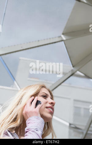 Low angle view of teenage girl talking on mobile phone, Munich, Bavaria, Germany - Stock Photo