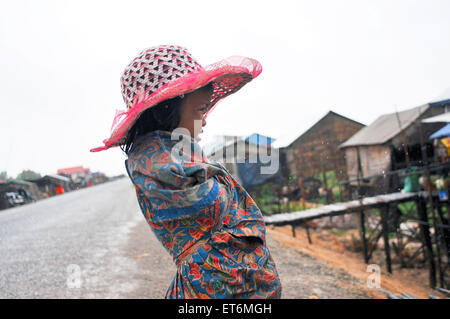 A cambodian girl in the rain at floating village on Tonle Sap Lake near Siem Reap, Cambodia. - Stock Photo