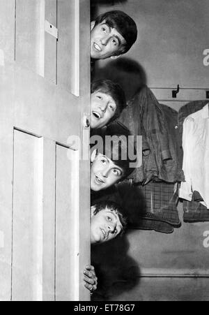 The Beatles peering out from behind their dressing room door before their appearance at the Odeon Theatre in Manchester. - Stock Photo