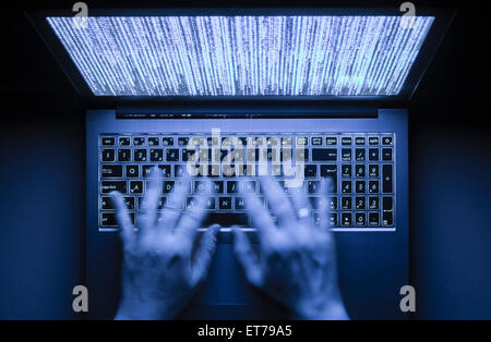 Hands are typing on a laptop computer in the dark with illuminated keyboard and mystic program code on screen