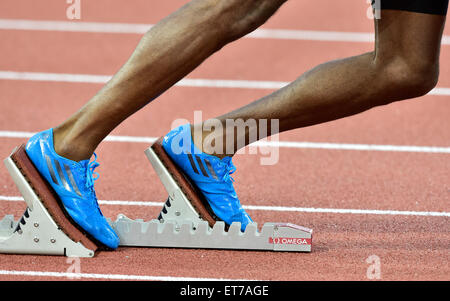 A male athlete (African ethnicity) is getting ready at the starting block on an athletics race track just before - Stock Photo