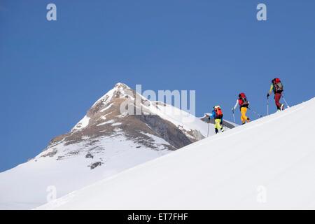 Ski mountaineers climbing on snowy peak, Tyrol, Austria - Stock Photo