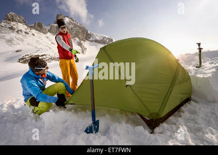 Young men building tent in snow, Tyrol, Austria - Stock Photo