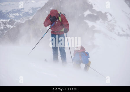 Ski mountaineers climbing on snowy mountain in snow storm, Zell Am See, Austria - Stock Photo