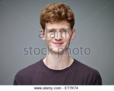 Portrait of smiling redheaded young man - Stock Photo
