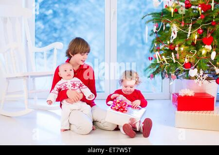 Three kids opening Christmas presents, enjoying Xmas morning in a living room with decorated tree and window into - Stock Photo