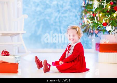 Cute curly little girl in a red dress and white pearl necklace playing under a Christmas tree with presents sitting - Stock Photo