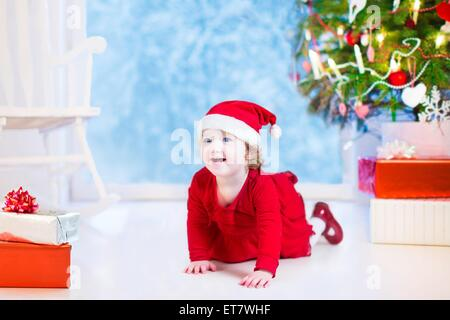Cute curly little girl in a red dress and Santa hat playing under a Christmas tree with presents sitting on the - Stock Photo
