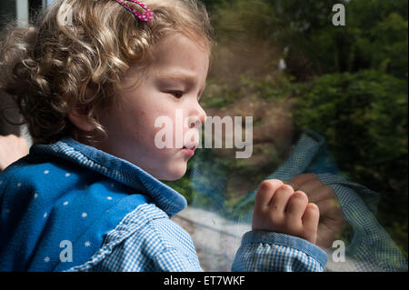 Berlin, Germany, a girl looks while riding the train out of the window - Stock Photo