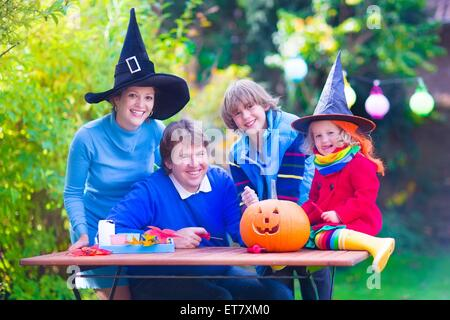 Happy family, parents with two children wearing witch costume and hat celebrating Halloween and pumpkin carving - Stock Photo