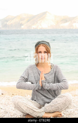 Teenage girl doing yoga on the beach, Baska, Croatia - Stock Photo