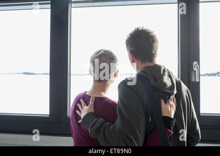 Rear view of couple looking out of window, Bavaria, Germany - Stock Photo