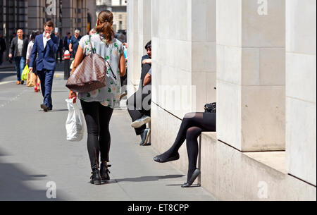 London, England, UK. People in the city, some relaxing in the sun at lunchtime - Stock Photo