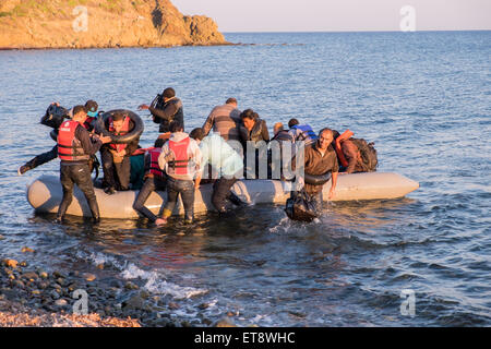 Syrian refugees cross from Turkey to land on a beach on the Greek island of Lesvos - Stock Photo