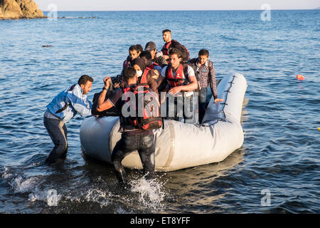 Refugees from Syria and Afghanistan reach the shores of the Greek island of Lesvos after crossing in rafts from - Stock Photo