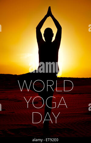 a young yogi man practicing the tree pose outdoors in backlight at sunset and the text world yoga day - Stock Photo