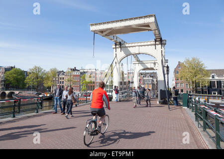 bikes on skinny bridge in amsterdam centre on sunny spring day - Stock Photo