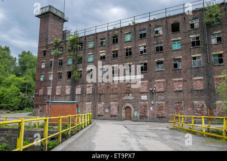 A Disused factory which has bricked up windows and door to the second floor - Stock Photo