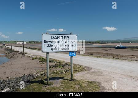 Tidal Road and warning sign at Sunderland Point - Stock Photo