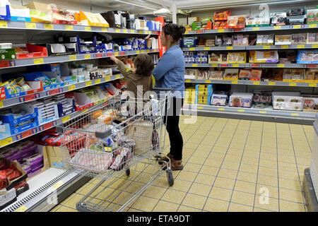 Mother and child shopping for yogurt in Aldi supermarket refrigeration aisle  UK  KATHY DEWITT