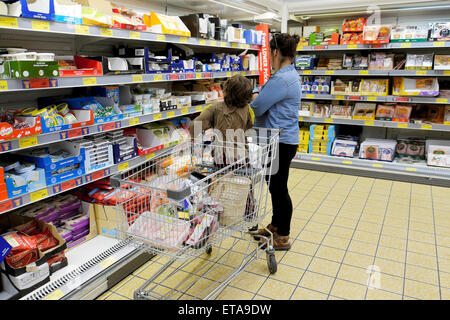 Mother and child shopping for dairy products  on shelves in Aldi supermarket cheese and yogurt refrigeration aisle  UK  KATHY DEWITT