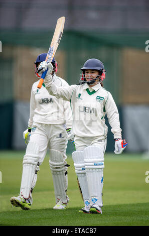 A batsman celebrates her 50 junior during a girls cricket match in Wiltshire UK - Stock Photo
