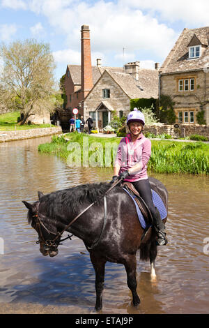 Watering the horse in the River Eye flowing through the Cotswold village of Lower Slaughter, Gloucestershire UK - Stock Photo