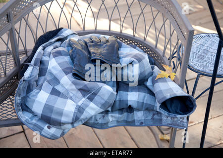 Plaid jacket and gloves on decorative wrought iron curved bench with autumn maple leaf. St Paul Minnesota MN USA - Stock Photo