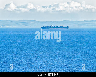 Ocean going container ship loaded with containers on deck sailing at sea - Stock Photo