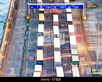 Line of trucks in sea port with many containers waiting to be shipped - Stock Photo