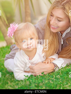 Cheerful young mother playing with her adorable little daughter in the park, lying down on fresh green grass field, - Stock Photo