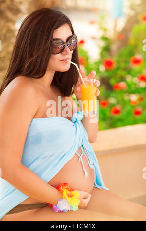 Beautiful pregnant woman sitting on tropical beach among exotic flowers and drinking tasty refreshing juice - Stock Photo
