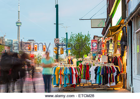 Toronto Chinatown in night time: Clothing sold on the streets of the multicultural city with the CN Tower in the - Stock Photo