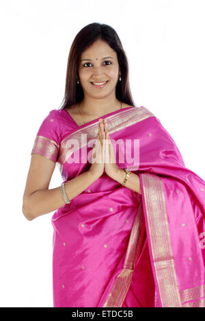 Portrait of beautiful Indian traditional woman greeting 'NAMASTE' - Stock Photo