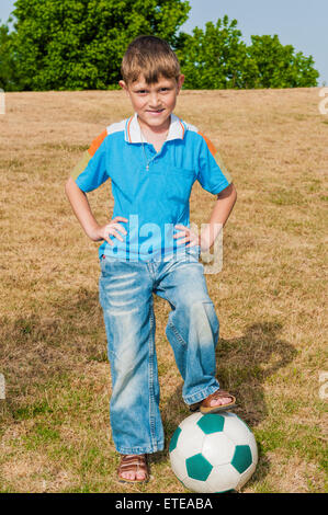 Little football player  has come to play football with his father in the park  and want to have to start the game - Stock Photo