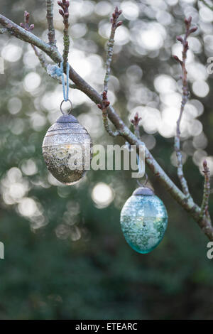Christmas glass decorations hanging outside on the branch of a tree. Back lighting has caused a bokeh effect behind - Stock Photo