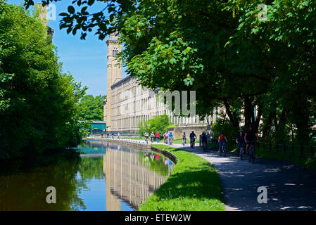 Cyclists on towpath of Leeds and Liverpool Canal, and Salt's Mill, Saltaire, West Yorkshire, England UK - Stock Photo