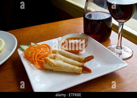 Fried prawns wrapped in pastry skin with plum sauce. Prawn presented with carrot and cucumber garnish on side on - Stock Photo
