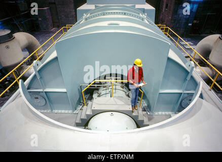 Male engineer inspecting drawings near a steam turbine, nuclear power plant in Pennsylvania, USA - Stock Photo