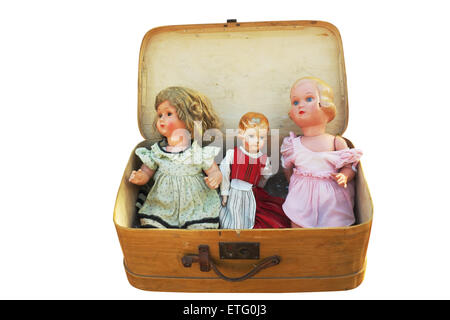 three vintage doll in an old wooden suitcase - Stock Photo