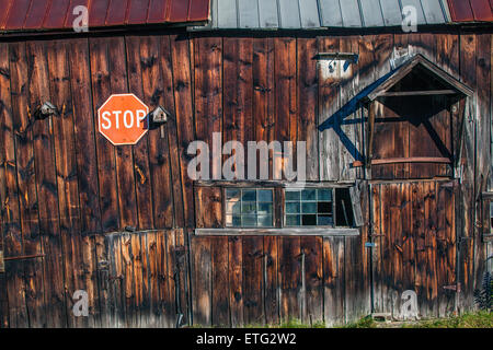 The side of an old, wooden barn with dark, reddish-brown colored wood, bird houses, stop sign and old windows. Study - Stock Photo