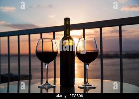 Silhouette of bottle and glasses with red wine in sunset with sea view background - Stock Photo