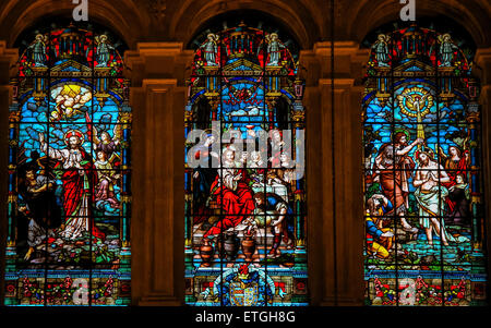 Stained glass window depicting Jesus casting away Lucifer, Jesus at the Wedding at Cana and Jesus baptized in the - Stock Photo