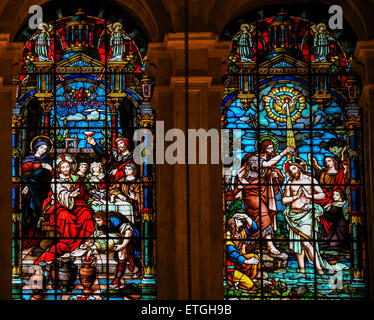 Stained glass window depicting, on the left, Jesus at the Wedding at Cana, and, on the right, Jesus baptized in - Stock Photo